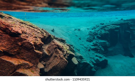 Pure clear glacial water in Iceland national park Thingvellir, Silfra fissure swimming between two tectonic plates. Lava colorful rocks formations, beautiful background