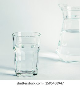 Pure clear water in a glass glass and glass jug stands on a white background