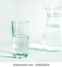 Pure clear water in a glass and jug stands on a white background