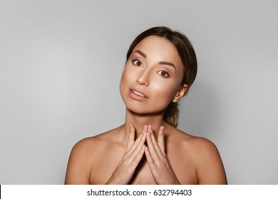Pure confidence. Close-up of a beautiful young woman without a shirt, holding her hands under her chin, standing on a white background