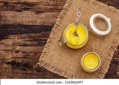 Pure or desi ghee (ghi), clarified melted butter. Healthy fats bulletproof diet concept or paleo style plan. Glass jars, silver spoon on vintage sackcloth. Wooden boards background copy space top view