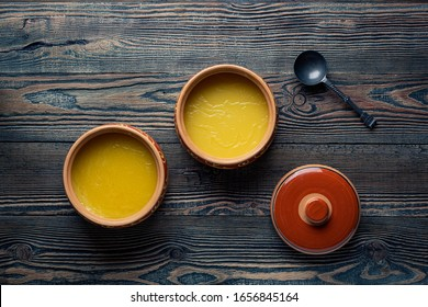 Pure OR Desi Ghee also known as clarified liquid butter. Pure OR Desi Ghee in ceramic bowls on an old wooden table.