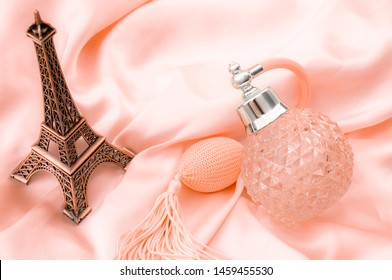 Pure essence perfumes, fragrance of France and romantic mood in Paris concept theme with a vintage bottle of french perfume on pink silky satin or silk next to miniature replica of the Eiffel Tower
