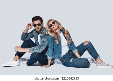 Pure feelings. Beautiful young couple in denim wear bonding and smiling while sitting against grey background