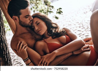 Pure feelings.  Handsome young man embracing young attractive woman in red bikini while resting on the beach together