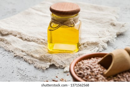 Pure linseed oil in bottle and bowl of linseeds on concrete background.