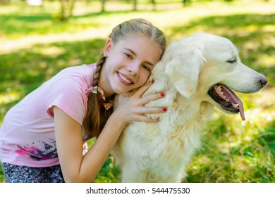 Pure love of a child who embrace her favorite pet - golden retiever with an amazing fur. Girl looks right in the camera with spread happy smile.