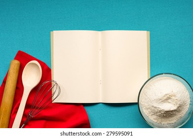 Pure notebook for recording menu, recipe on blue tablecloth with red napkin and kitchen utensils. Close- up view from top.