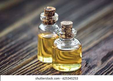 Pure organic aroma essential oil in glass bottle isolated on wooden background beauty treatment. Fragrant oil spa concept wellness setting. Selective focus macro front view horizontal. Place for text.