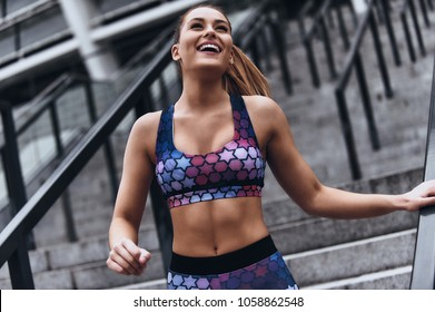 Pure perfection. Attractive young woman in sport clothing smiling and looking away while exercising outdoors