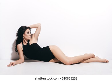 Pure perfection. Attractive young woman in black swimsuit holding hand in hair and looking away while lying in front of white background