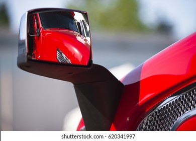 Pure reflection of modern red semi truck in his own rear-view mirror and the bonnet of the truck with chrome grille on the background blurry parking details