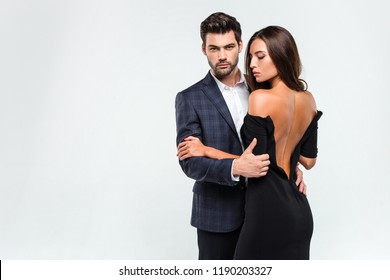 Pure seduction. Young beautiful couple bonding and looking at camera while standing against white background