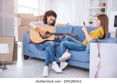 Pure talent. Charming young girl sitting on the sofa next to her roommate and filming her playing guitar