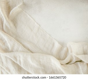 Pure washed linen cloth on light grunge stone background. Natural washed linen fabric on stone tile surface with copy space.