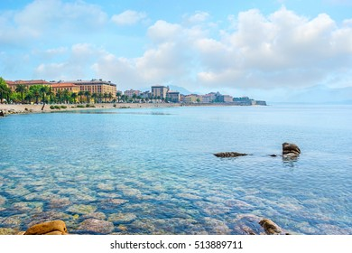 The pure waters expose the rocky seabed at the Ajaccio coast with the old town buildings on the background, Corsica, France.