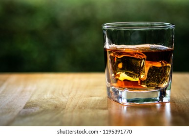 Pure whiskey on the wood table with nature background