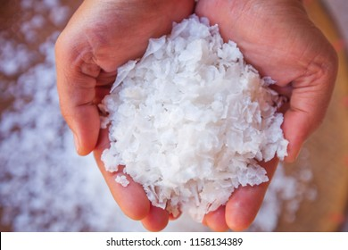Pure white crystals salt, rock salt in woman hands on crystals backgrounds. Top view, close-up. Traditional rock salt making of Bo Kluea, Nan, Thailand. Ancient salt pits. Culture and History.