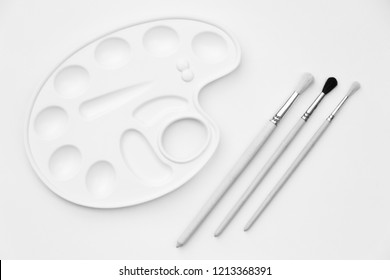 Pure white palette and three new artist brushes on a white background. Close-up. Black and white photography. Background.