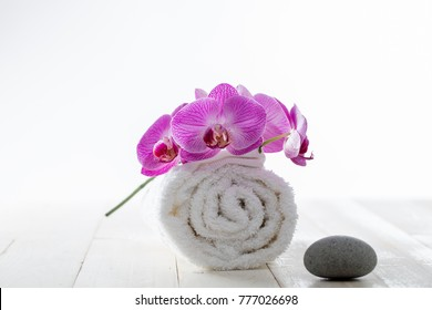 pure white rolled up towel with pink orchids and zen pebble for concept of beauty spa and healthy wellbeing, chic still life, white background