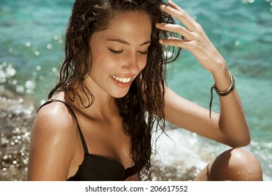 Pure woman beauty with wet hair and bright make up. Smiling beauty . Toned in warm colors. horizontal shot on the beach.