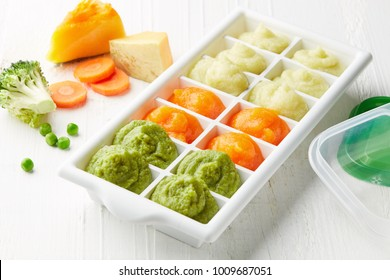 Pureed baby food in ice cube trays ready for freezing on white wooden table