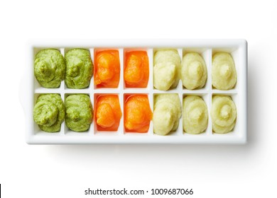 Pureed baby food in ice cube trays ready for freezing isolated on white background, top view