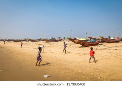 Puri, India - Circa January, 2018. Kids playing cricket on the sandy beach with fishing boats on the background in Puri.