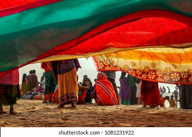 Puri, Odisha, India - January 9, 2014 - Indian women pilgrims drying their colorful sarees under sun after taking holy bath at puri beach.