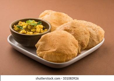 Puri/Bhaji - Indian semi dry Potato Spicy recipe also known as Batata or Aloo ki Sabji, served with fried Poori. Selective focus