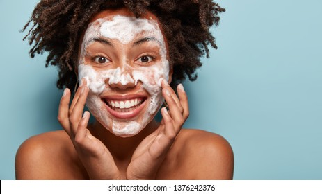 Purification of face. Happy smiling woman washes face with soap, cleans pores, touches cheeks, has spa procedures, uses gel, shows naked shoulders, isolated over blue background with blank space