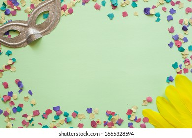 Purim carnival green background with colorful confetti, yellow feathers and grey glitter mask