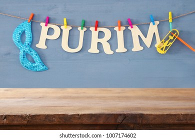 Purim celebration concept (jewish carnival holiday) in front of empty wooden table. product display backdrop