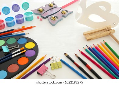 Purim celebration concept (jewish carnival holiday). Mask coloring fun artwork leisure and painting accessories: watercolors, colorful pencils, acrilic colors and brushes