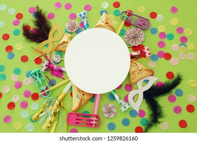 Purim celebration concept (jewish carnival holiday) over green wooden background. Top view
