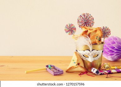 Purim celebration concept (jewish carnival holiday) over wooden table