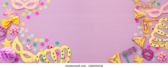 Purim celebration concept (jewish carnival holiday) over wooden pink background. Banner