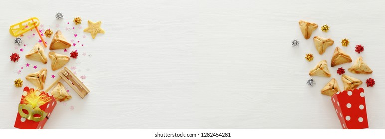 Purim celebration concept (jewish carnival holiday) over wooden white background. Banner