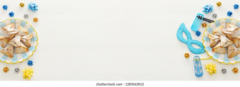 Purim celebration concept (jewish carnival holiday) over wooden white background