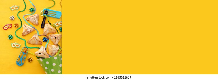 Purim celebration concept (jewish carnival holiday) over wooden yellow background. Banner
