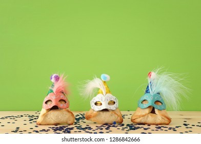 Purim celebration concept (jewish carnival holiday). Traditional hamantaschen cookies with cute clown hats and masks over wooden table and green background