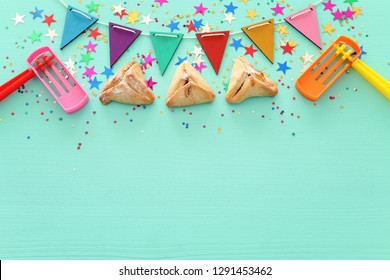 Purim celebration concept (jewish carnival holiday) over wooden mint background