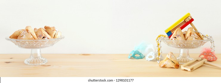 Purim celebration concept (jewish carnival holiday) over wooden table and white background