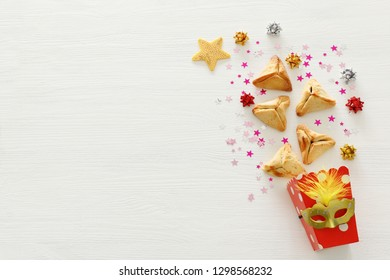 Purim celebration concept (jewish carnival holiday). Traditional hamantaschen cookies over white wooden table