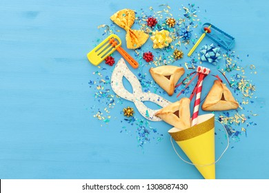 Purim celebration concept (jewish carnival holiday) over wooden blue background