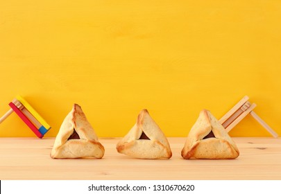 Purim celebration concept (jewish carnival holiday). Traditional hamantaschen cookies over wooden table and yellow background