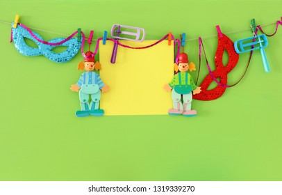 Purim celebration concept (jewish carnival holiday) with empty note for text, clown, mask and noisemaker over wooden green background