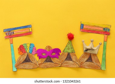 Purim celebration concept (jewish carnival holiday). Traditional hamantash cookies cutted from paper and painted