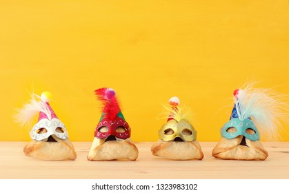 Purim celebration concept (jewish carnival holiday). Traditional hamantaschen cookies with cute masks over wooden table and yellow background