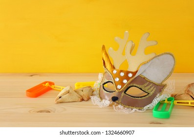 Purim celebration concept (jewish carnival holiday) with cute deer/bambi mask, noisemaker and hamantash cookies over wooden table
